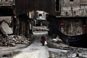 """Anziana signora siriana attraversa la """"via dei cecchini"""" della città vecchia di Aleppo. ©Fabio Bucciarelli-AFP"""